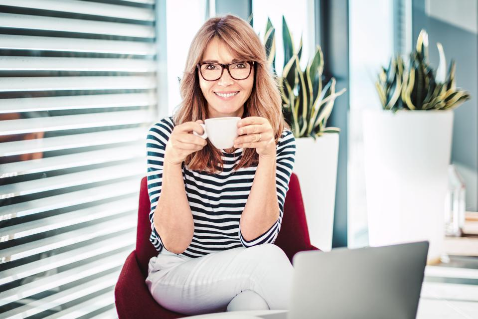Happy woman drinking coffee while sitting at home and working online