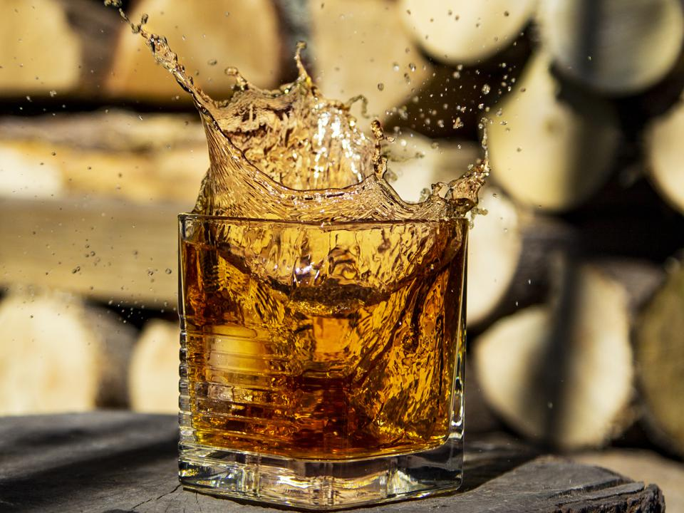 Whiskey splash in glass on a wooden background