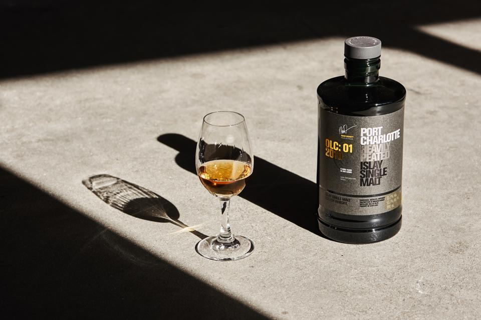 Glass of Bruichladdich Port Charlotte OLC:01 2010 Heavily Peated Scotch next to bottle