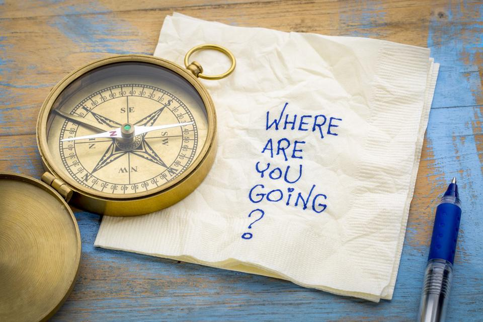 compass open on a table next to a pen and a napkin, written on it ″Where are we going?″