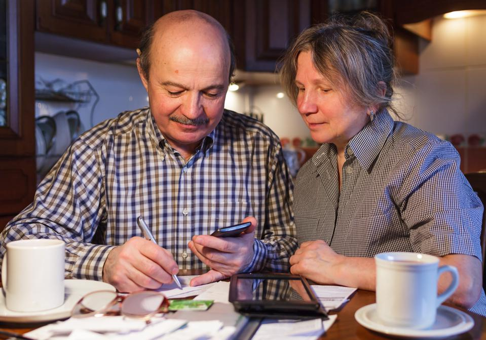 Couple at kitchen table with calculator and financial statements.