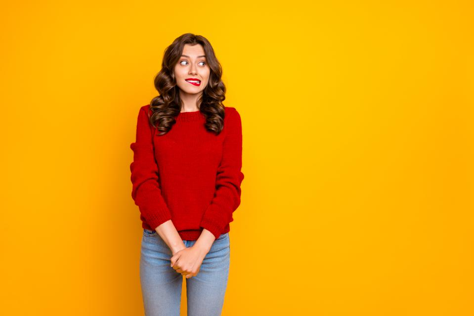 Photo of pretty curly wavy charming cute cheerful nice good girlfriend standing hesitating and shy looking away at something with hands folded isolated over yellow vivid color background