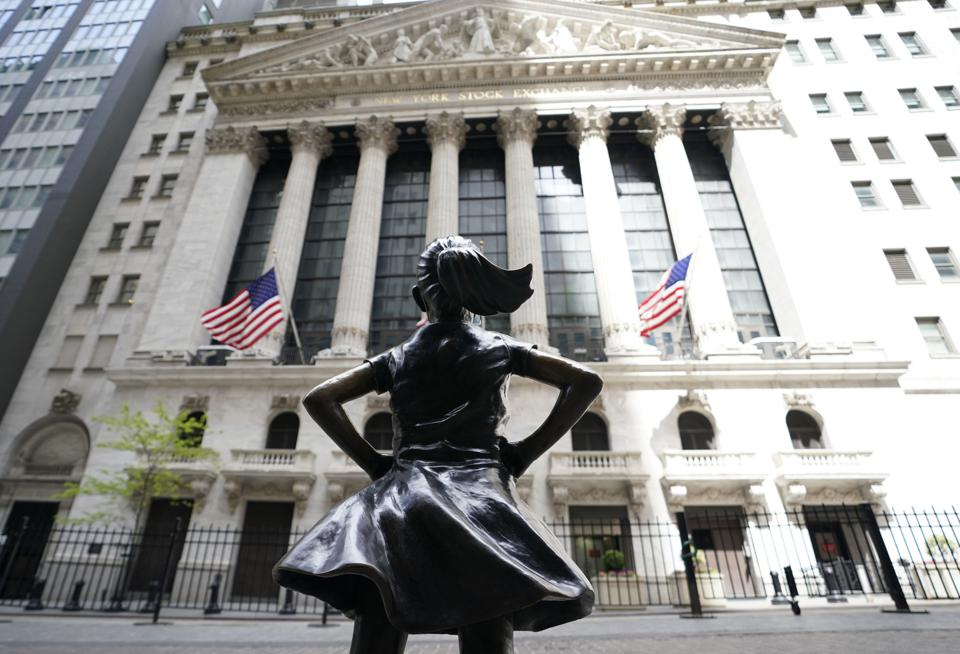 The Fearless Girl looks up defiantly at the Stock Exchange building.