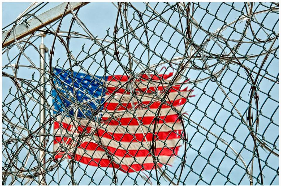 An American flag behind a barbed wire fence.
