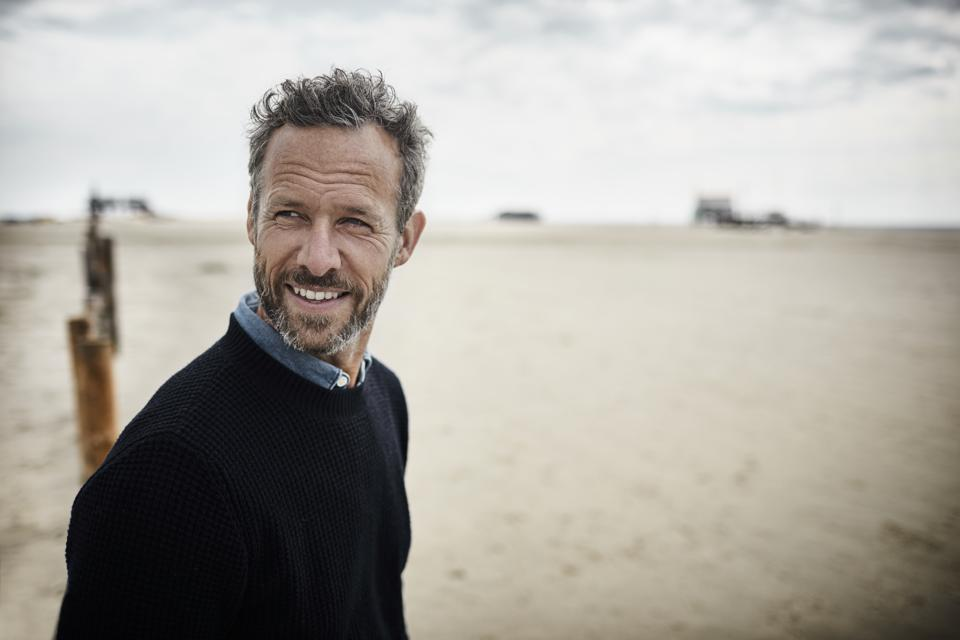 Portrait of smiling bearded man on the beach