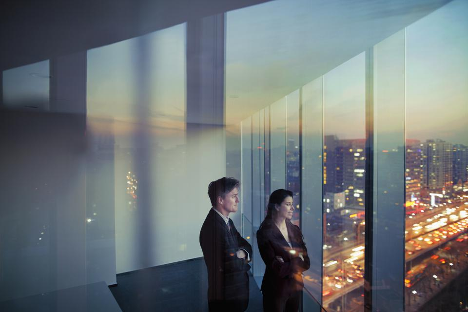 Business colleagues looking out window in office