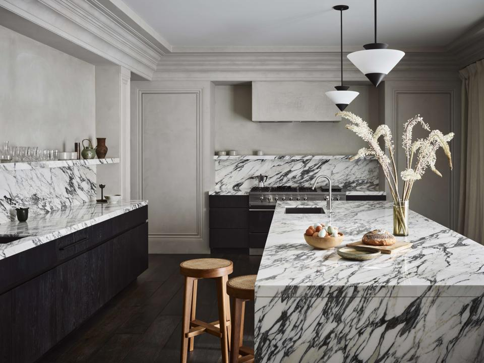 The kitchen, with a large marble island in the center and marble backsplashes and shelving.