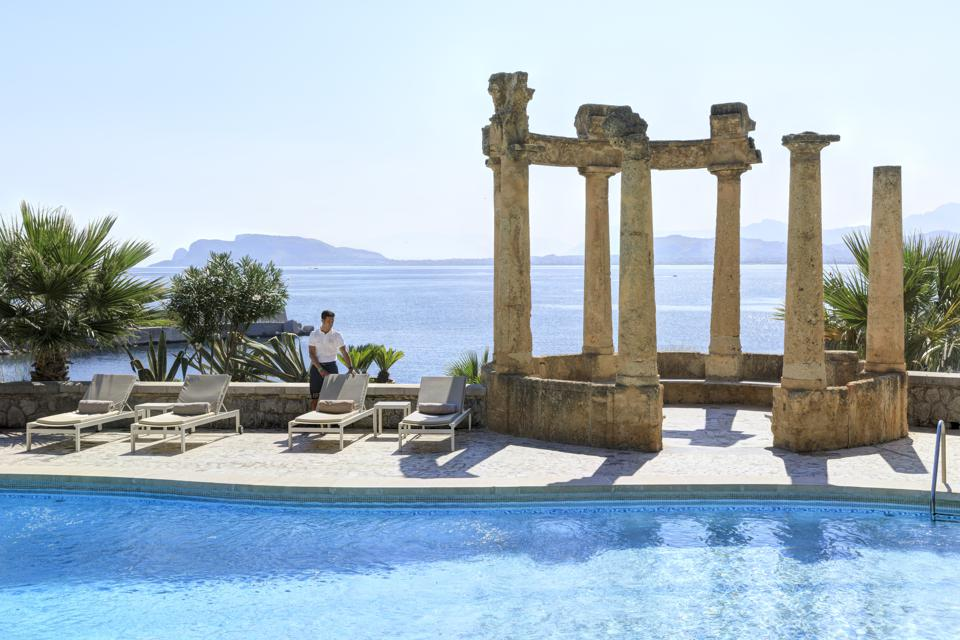 Roman columns next to the pool at Villa Igiea luxury boutique hotel Sicily.