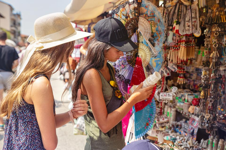 Friends and sisters sightseeing in Pisa, Italy, buying souvenirs in a Roamana store