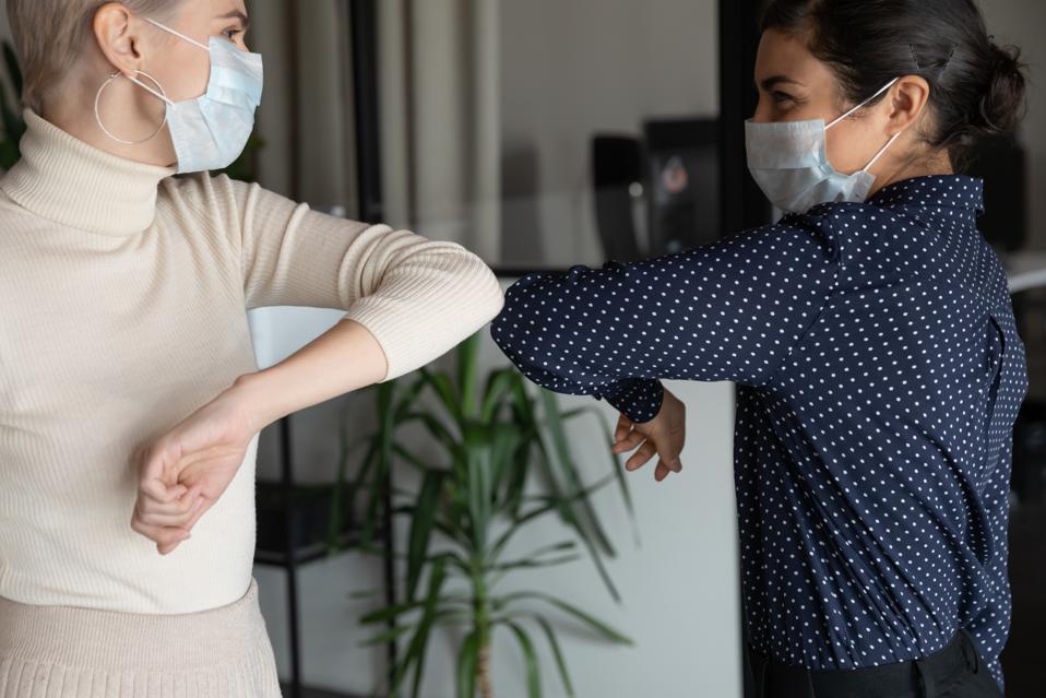 Healthy colleagues in facial masks bumping elbows.