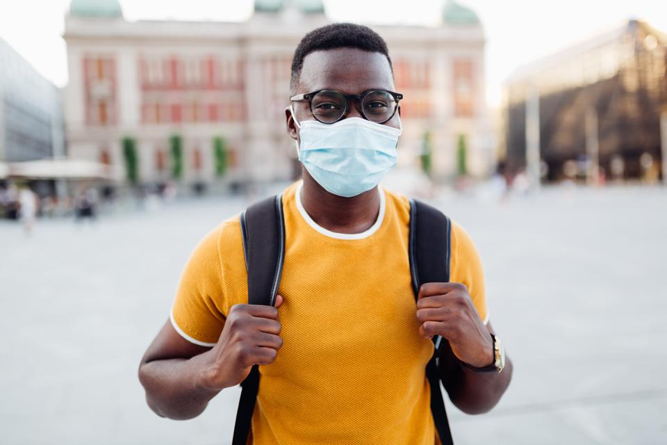 Portrait of a handsome young African American male student wearing a protective face mask