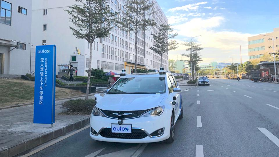 An AutoX driverless minivan with external lidar sensors parked at a curb in front of an AutoX pick-up stop in China.