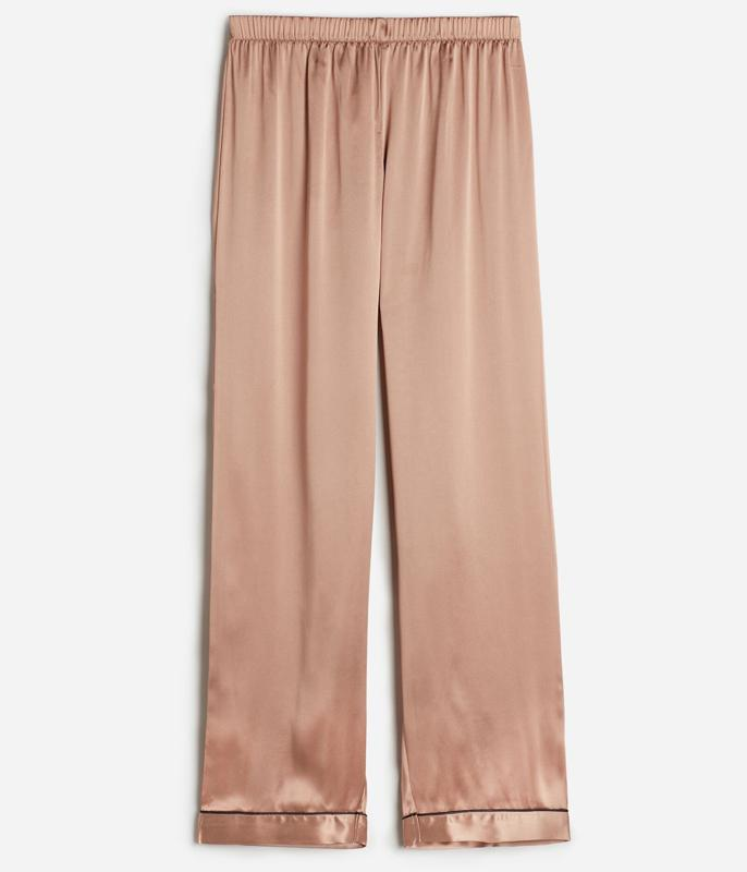 Silk satin pajama pants featuring a covered stretch waistband and contrast trim