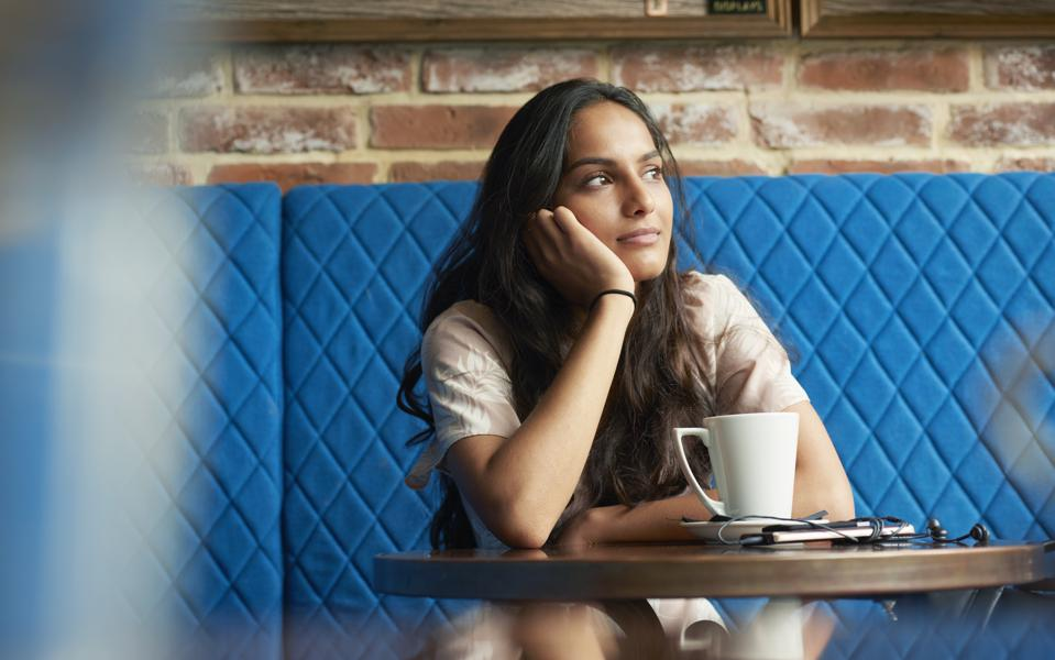 Woman sitting in contemplation at a cafe table