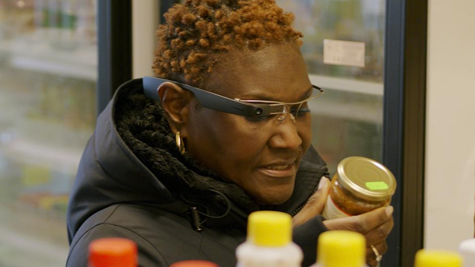 Woman in shop using Envision glasses to examine items on a shelf