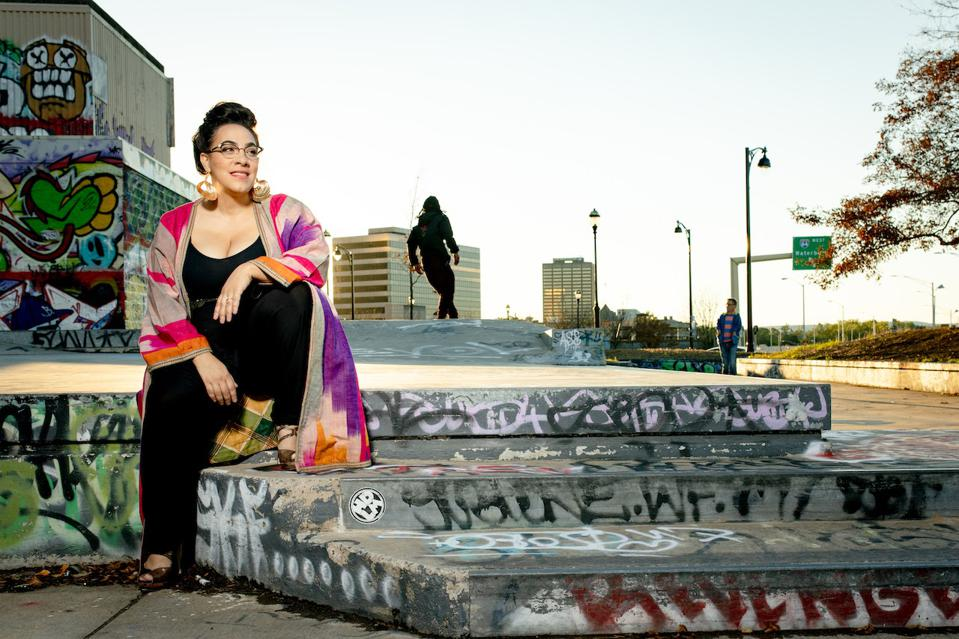 diverse woman sitting on the steps of a street
