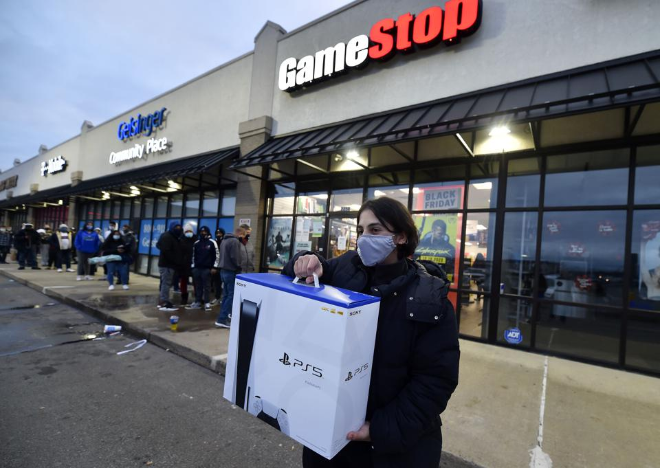 A man wearing a face masks leaves Game Stop with the new...