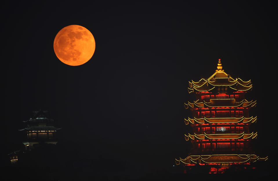 The full red moon rises over the Yellow Crane Tower during the penumbral lunar eclipse on November 30, 2020 in Wuhan, Hubei Province of China. (Photo by Zhou Guoqiang/VCG via Getty Images)