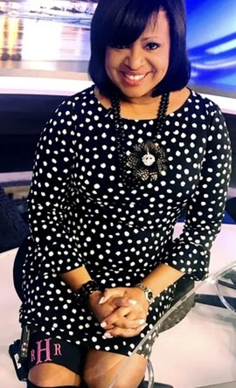 A Black woman in a black and white polka dot dress smiles on a television news set.