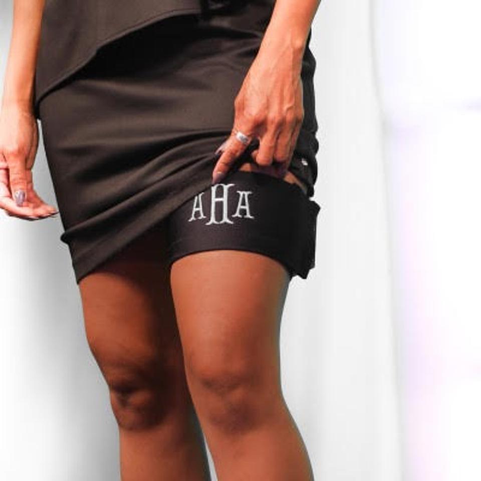 A Black woman's leg wearing a wrap that says ″AHA″