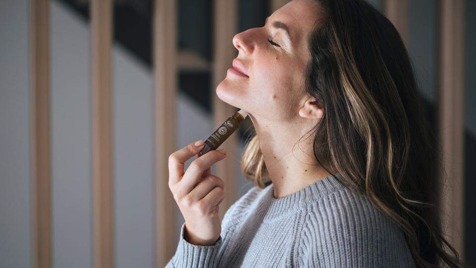 A white woman with brown hair applies Saje essential oil roll-on.