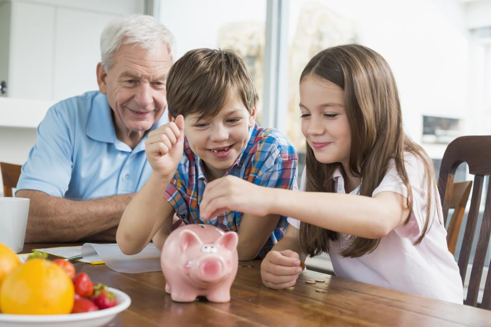 Two children and grandfather with piggy bank