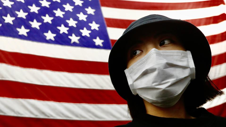 A Taiwanese woman seen next to a national flag of USA. The...