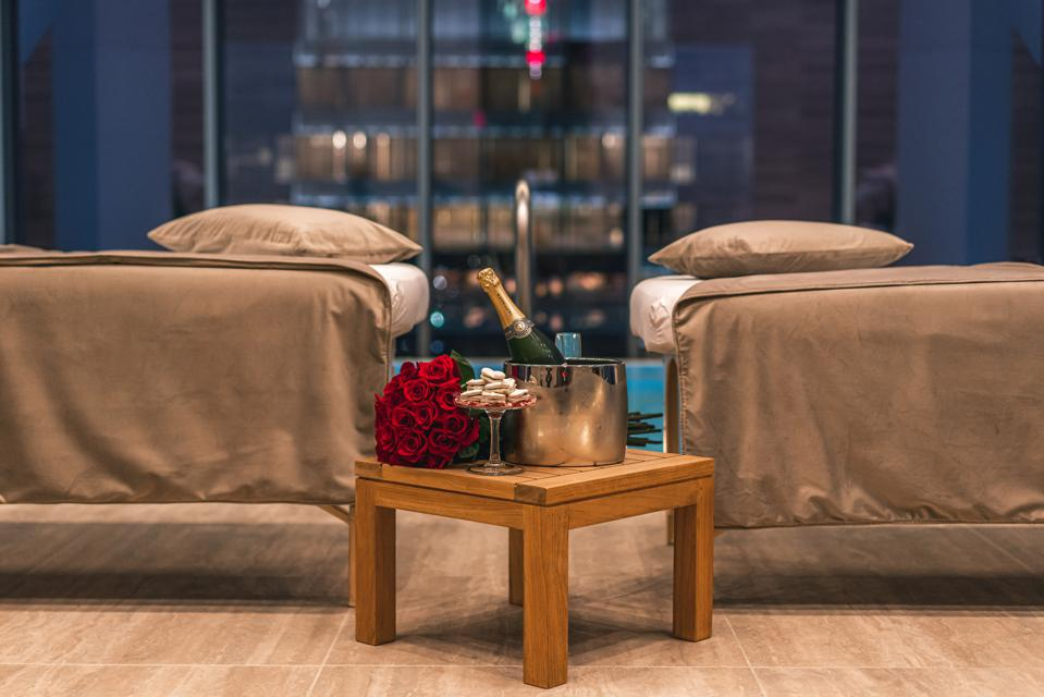 Two massage chairs are separated by a side table supporting champagne and roses.