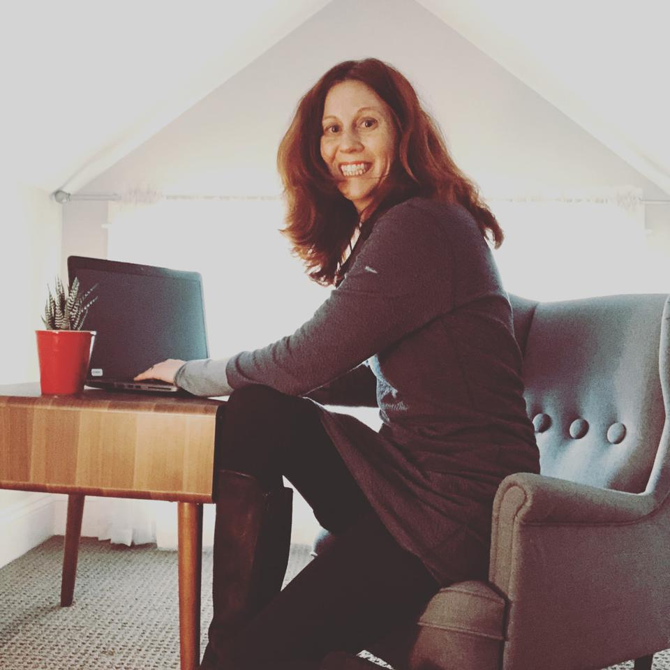 Author Megan Bledsoe sits at a desk, showing her working from home set up