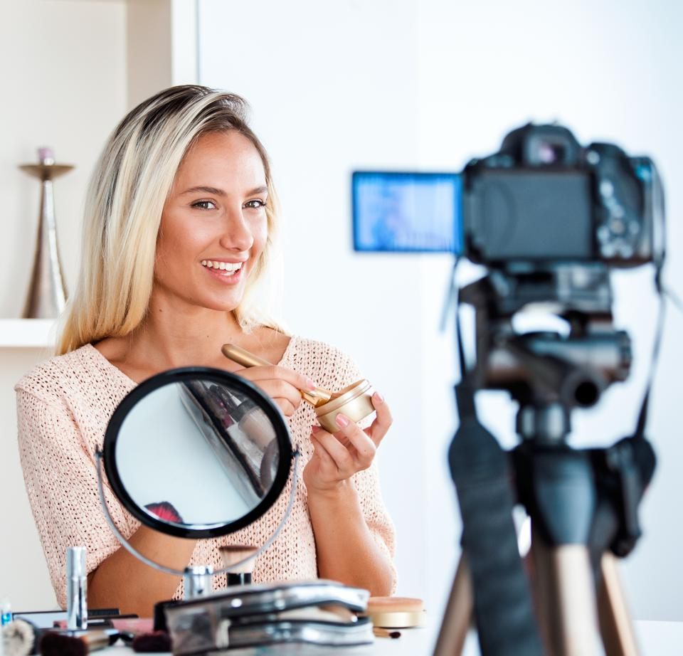 Female vlogger is showing cosmetic products and giving advices for her beauty blog.