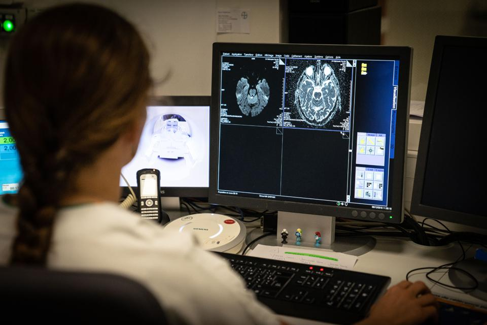 Healthcare provider looking at monitor with brain scan images.