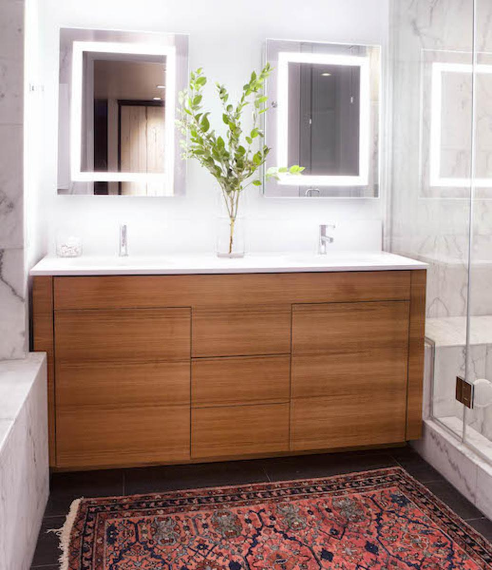 a marble bathroom with a red Persian rug, lit mirrors and wood vanity