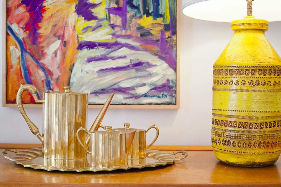 a wood table with gold tea set and yellow lamp