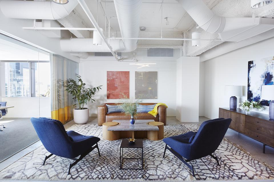 office waiting room with blue chairs and exposed pipes