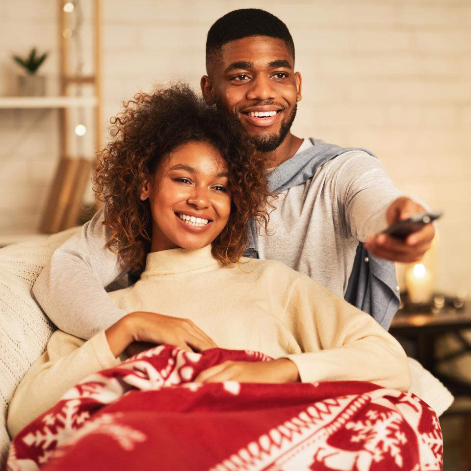 Afro couple in love at Christmas eve enjoy watching tv