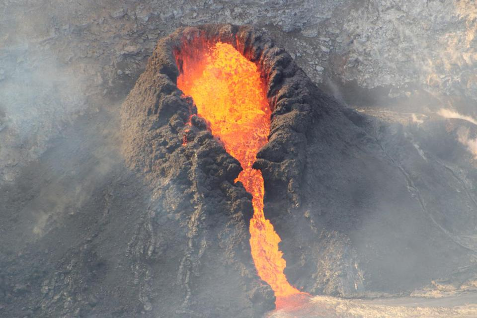 Lava gushes from a small cone atop Kīlauea volcano.