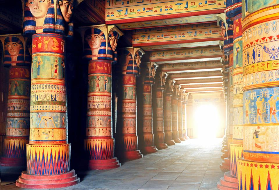 Light shines through a tunnel of colorful columns in the tombs at Luxor in Egypt