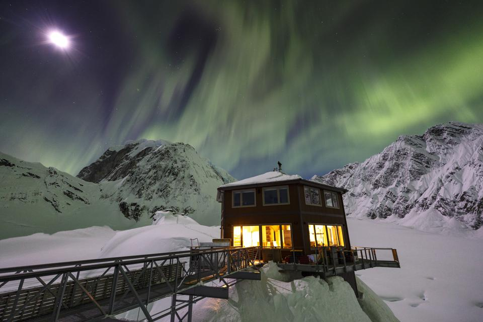Sheldon Chalet in Alaska is covered in snow and the northern lights are visible overhead
