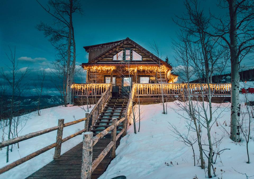 The cabin on Snowmass Mountain in Colorado is decorated with lights and surrounded by snow