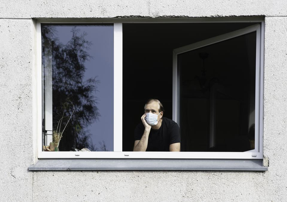 A man wearing a face mask looking out of a window.