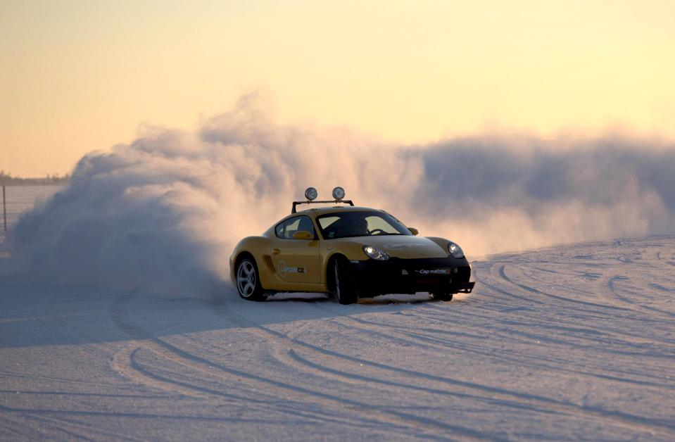 A car fishtails in the snow in during a session of extreme ice driving in the Arctic