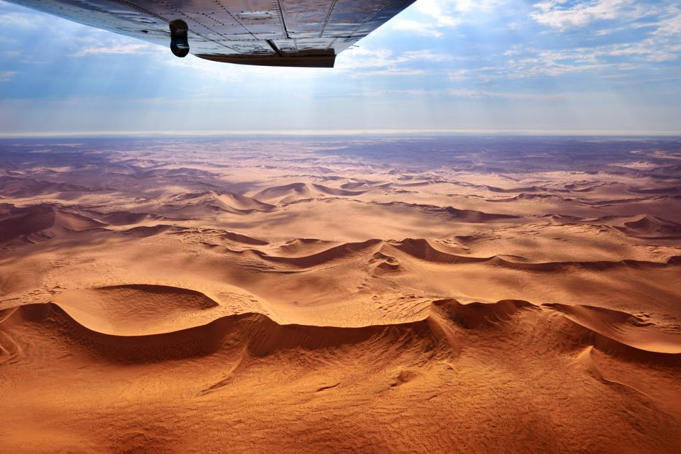 The sand dunes of Namibia are seen from above, stretching out beneath a bright blue sky