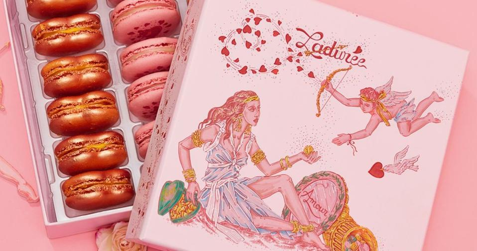 Laduree macarons in pink and bronze in a box decorated with cupid