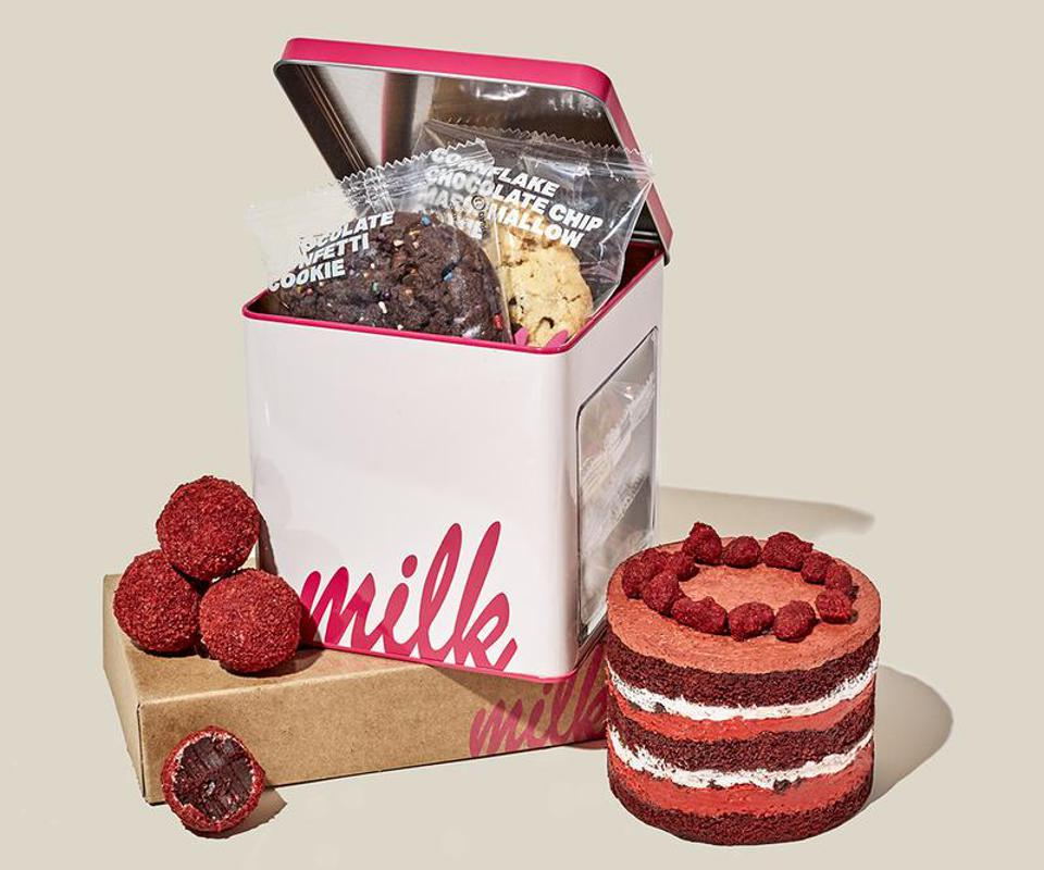 A mini red velvet layer cake, cake truffles, and a tin of assorted cookies
