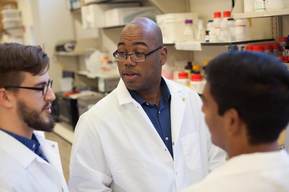 A bald Black man with glasses wearing a lab coat looks to the left talking to two male students in lab coats