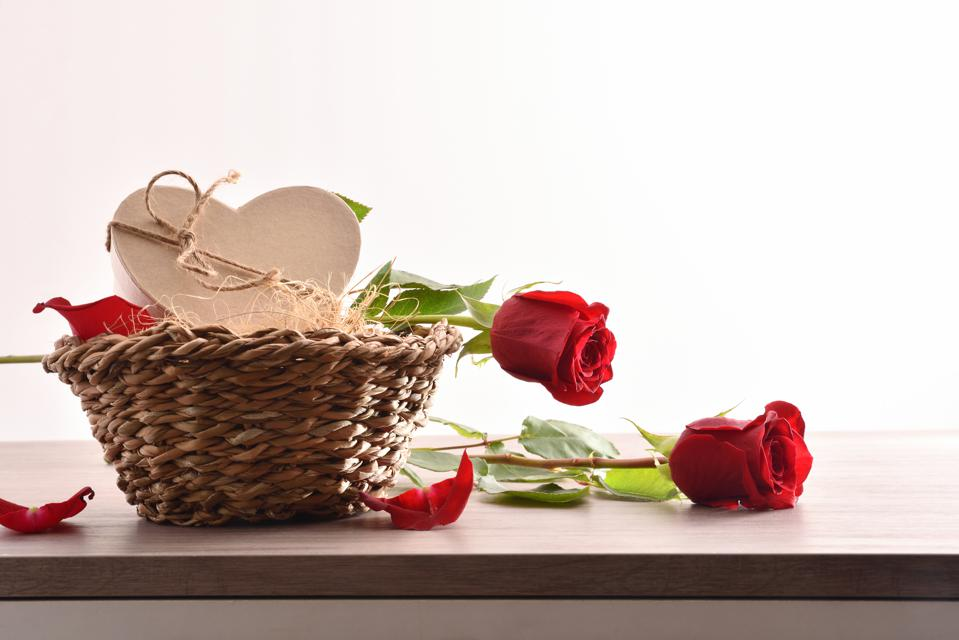 Gift on wicker basket and roses on wood table front