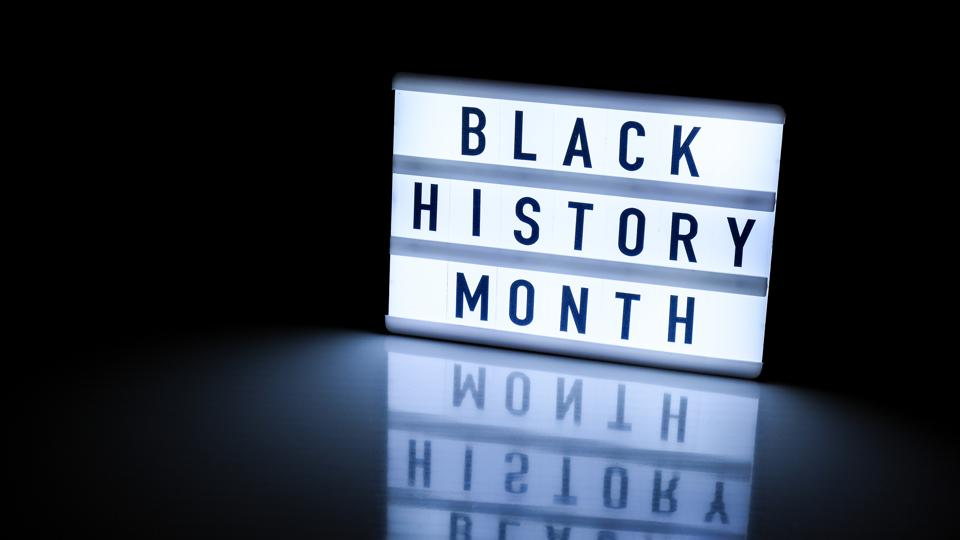Lightbox with text BLACK HISTORY MONTH on dark black background with mirror reflection. Message historical event