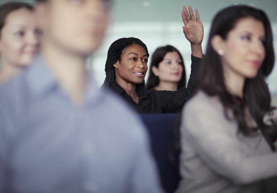 Woman raising hand in group seminar workshop