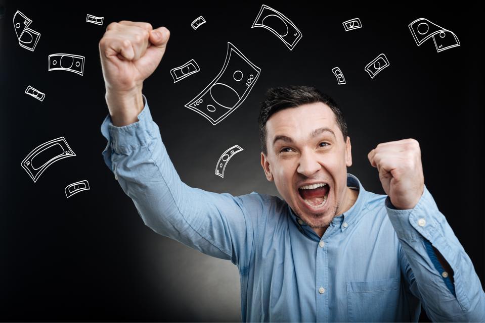 Pria tampan yang sangat gembira dengan kemeja biru merayakan kemenangan jackpot