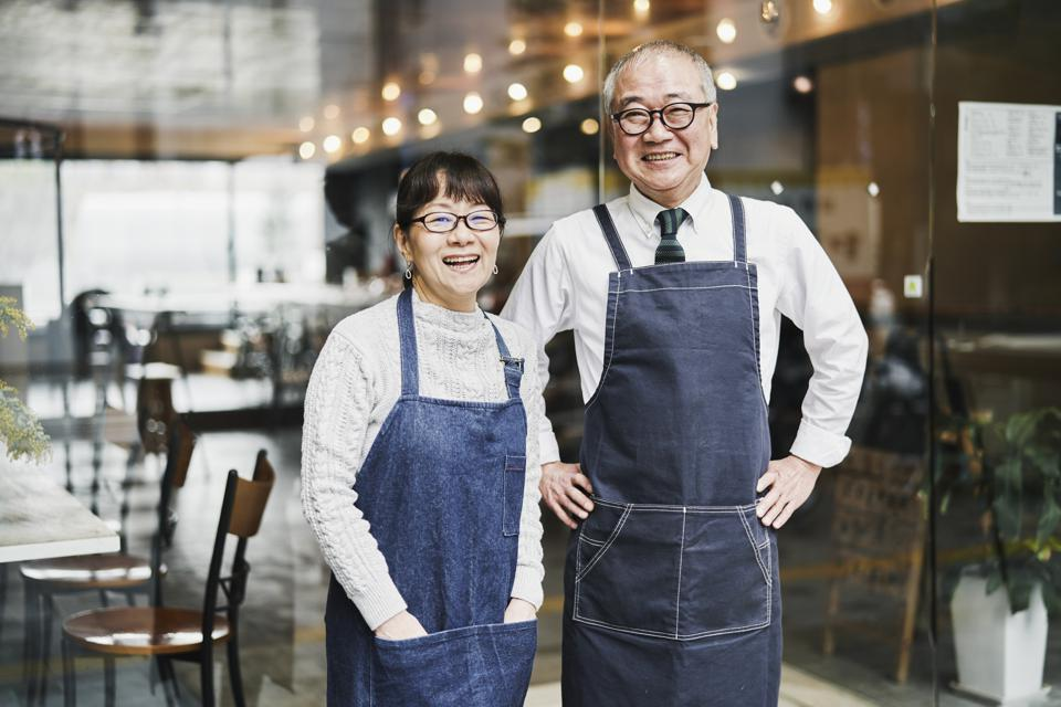 Senior couple cafe owners working happily in cafe together